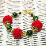 Gylden armbånd med røde heklede og grønne perler