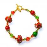 Armbånd med røde og grønne lampwork glassperler med blomster