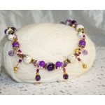 Gylden halssmykker med lilla perler, hvite lavaperler, stardust perler og hvite bånd