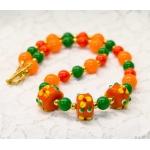 Oransje halssmykke med grønne og lampwork-perler