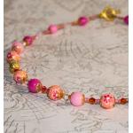 Gylden halssmykke med gylne stardust og rosa fibo perler