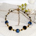 Gylden halssmykker med blå og svarte heklede perler