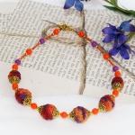 Gylden halssmykker med oransje og lille heklede perler