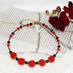 Gylden halssmykker med røde heklede og svarte perler