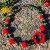 Gylden halssmykker med rød heklet blomst og grønne perler