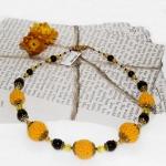 Gylden halssmykker med gule heklede og svarte perler